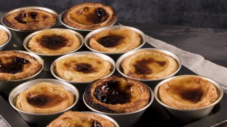 bafat : Rows of freshly cooked egg tarts, traditional portuguese dessert, pastel de nata, custard tarts on metal tray. Dostupné videozáznamy