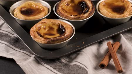 bolinhos : Rows of freshly cooked egg tarts, traditional portuguese dessert, pastel de nata, custard tarts on metal tray. Stock Footage