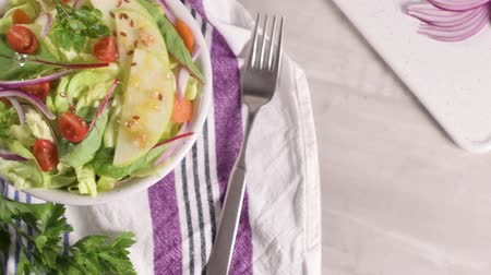 pano : Delicious vegetable salad with apple slices  in ceramic bowl on table. Stock Footage