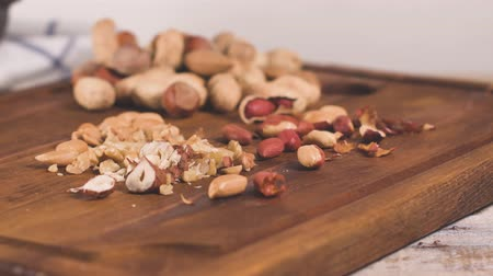 avellana : Nueces, avellanas, cacahuetes y nueces en la mesa de madera. Archivo de Video