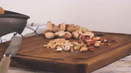 avelã : Walnuts, hazelnuts, peanuts and nuts on wooden table.