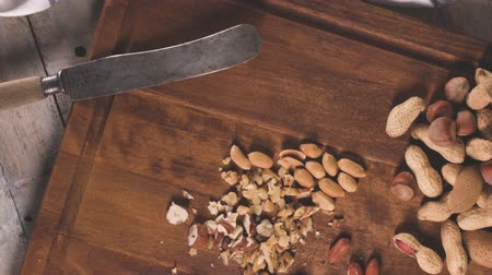 avellano : Nueces, avellanas, cacahuetes y nueces en la mesa de madera. Archivo de Video