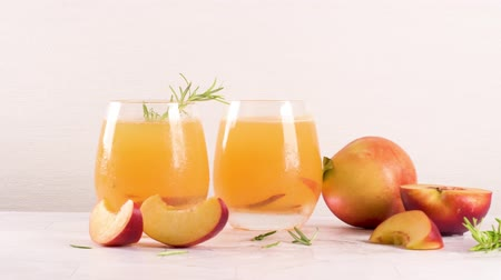 limonádé : Homemade peach juice with ice cubes and rosemary leaves in glass on marble stone background.