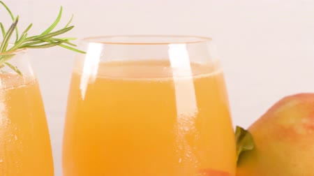 нектарин : Homemade peach juice with ice cubes and rosemary leaves in glass on marble stone background.
