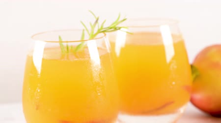 damascos : Homemade peach juice with ice cubes and rosemary leaves in glass on marble stone background.