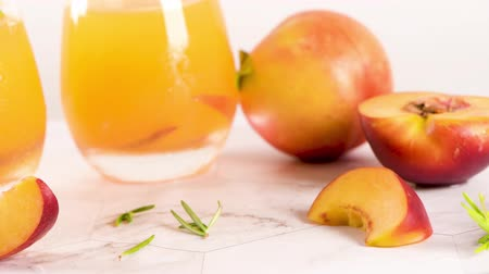 nektarinka : Homemade peach juice with ice cubes and rosemary leaves in glass on marble stone background.