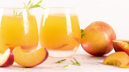 glass pitcher : Homemade peach juice with ice cubes and rosemary leaves in glass on marble stone background.