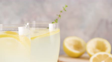 pitcher : Cold lemonade or alcoholic cocktail with lemon, rosemary and ice in glass glasses on a light background. Stock Footage
