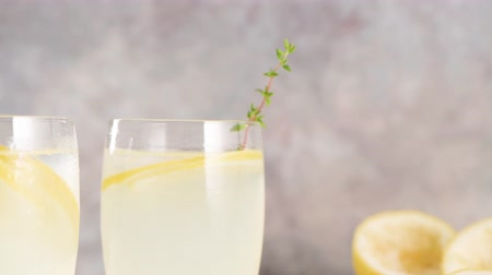 glass pitcher : Cold lemonade or alcoholic cocktail with lemon, rosemary and ice in glass glasses on a light background. Stock Footage