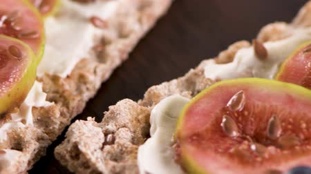 стартер : Canape or crostini with multigrain  crispread with cream cheese and fresh fig slices on a wooden board. Delicious appetizer ideal as an aperitif.
