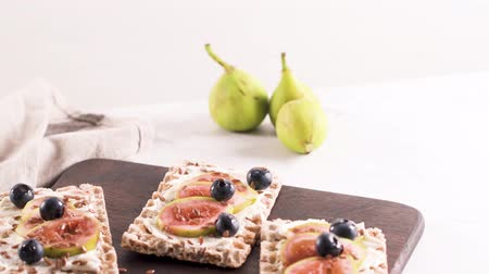 kakukkfű : Canape or crostini with multigrain  crispread with cream cheese and fresh fig slices on a wooden board. Delicious appetizer ideal as an aperitif.