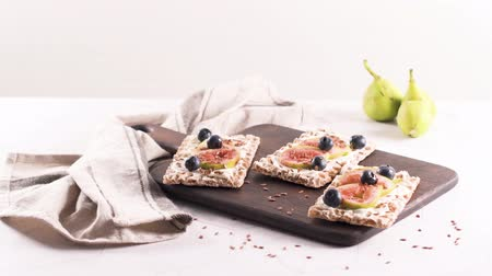 crostini : Canape or crostini with multigrain  crispread with cream cheese and fresh fig slices on a wooden board. Delicious appetizer ideal as an aperitif.