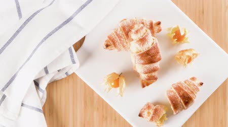 rogalik : Small croissant with physalis fruits in white ceramic tray, homemade cakes on wooden table top. Wideo
