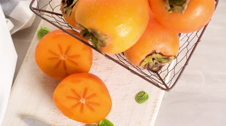 persimmons : Delicious fresh persimmon fruit on kitchen countertop. Stock Footage