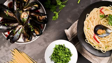 shellfish dishes : Homemade pasta spaghetti with mussels , peppers and parsley on rustic background. sea food meal. Stock Footage