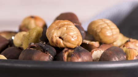 пульпа : Roasted chestnuts in cast iron pan over rustic wooden board and grey wooden background, selective focus. Стоковые видеозаписи