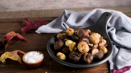 kaštanová : Roasted chestnuts in cast iron pan over rustic wooden board and grey wooden background, selective focus. Dostupné videozáznamy