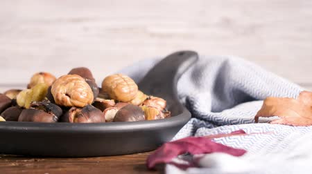 pan fried : Roasted chestnuts in cast iron pan over rustic wooden board and grey wooden background, selective focus. Stock Footage