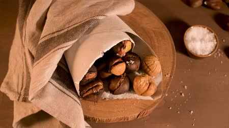 вегетарианство : Roasted chestnuts in a paper cone, on a rustic kitchen countertop.