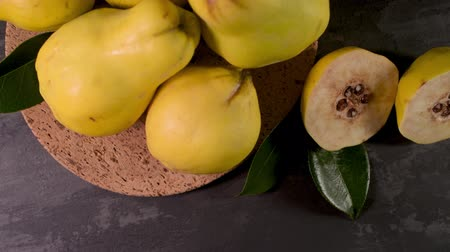 pigwa : Ripe yellow quinces or queen apple fruits and sliced quince halves with seeds in craft cork plates on black rustic background.
