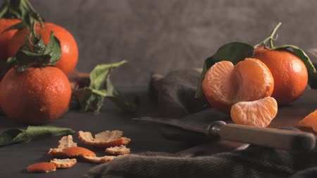 tangerina : Fresh mandarin oranges or tangerines with leaves on textured dark background Vídeos