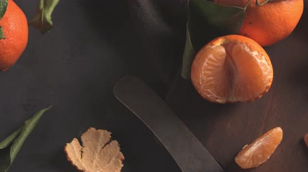 очищенные : Fresh mandarin oranges or tangerines with leaves on textured dark background Стоковые видеозаписи