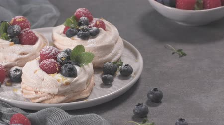 ягода : Small pavlova cakes with fresh raspberries and blueberries. Стоковые видеозаписи