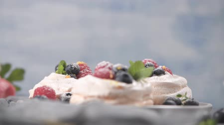 konfekció : Small pavlova cakes with fresh raspberries and blueberries. Stock mozgókép