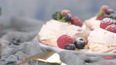 pavlova : Small pavlova cakes with fresh raspberries and blueberries. Stock Footage