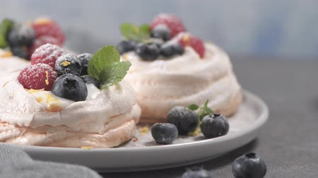 lamponi : Small pavlova cakes with fresh raspberries and blueberries. Filmati Stock