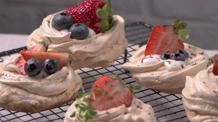 konfekció : Small pavlova cakes with fresh Strawberries and blueberries.