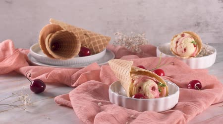 cold desert : Traditional waffle cones with ice cream and cherry fruits on marble stone surface.