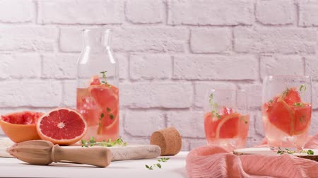 lemoniada : Healthy summer drink grapefruit lemonade with thyme in glasses with ice on a wooden surface.