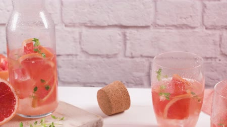 tomilho : Healthy summer drink grapefruit lemonade with thyme in glasses with ice on a wooden surface.
