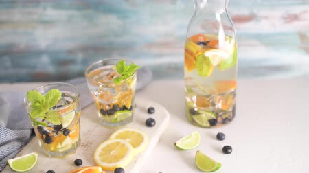 lemoniada : Summer healthy cocktails of citrus infused waters, lemonades or mojitos, with lime lemon orange blueberries and mint, diet detox beverages, in glasses on light background.