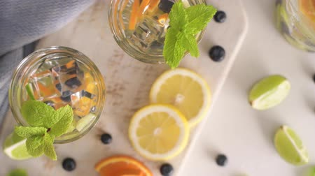 infused water : Summer healthy cocktails of citrus infused waters, lemonades or mojitos, with lime lemon orange blueberries and mint, diet detox beverages, in glasses on light background.