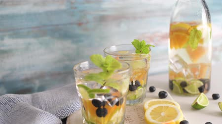 águas : Summer healthy cocktails of citrus infused waters, lemonades or mojitos, with lime lemon orange blueberries and mint, diet detox beverages, in glasses on light background.