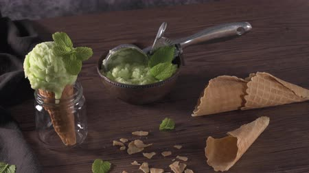 pisztácia : Pistachio ice cream in a dark rustic bowl and waffle cone on a brown wooden background. Stock mozgókép