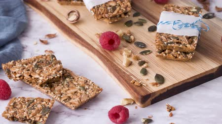 клюква : Organic homemade granola bars on rustic marble stone kitchen countertop. Стоковые видеозаписи