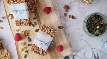 изюм : Organic homemade granola bars on rustic marble stone kitchen countertop. Стоковые видеозаписи