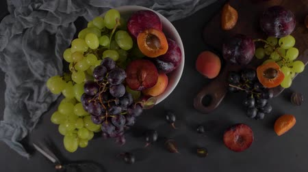 meruňky : Fruits Still life with fruit on white ceramic bowl. Concrete wall. Dramatic light. Grapes, apricots and plums. Dostupné videozáznamy