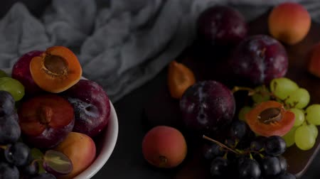 winogrona : Fruits Still life with fruit on white ceramic bowl. Concrete wall. Dramatic light. Grapes, apricots and plums. Wideo