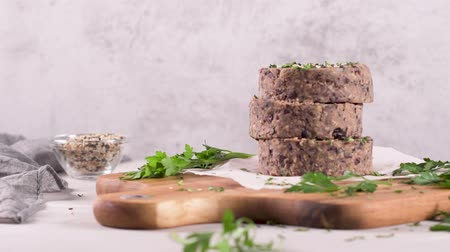 betterave : Raw veggie burger with black beans with parsley leaves on wood cutting board.