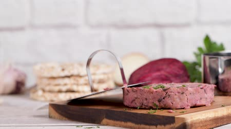 burak : Raw veggie burger with beetroot and white beans with parsley leaves on wood cutting board.