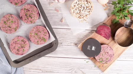 pancar : Raw veggie burger with beetroot and white beans with parsley leaves on wood cutting board.