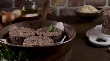 burak : Raw veggie burger with black beans with parsley leaves on wood countertop. Wideo