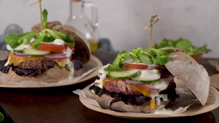 全粒 : Healthy vegan burger with fresh vegetables and yogurt sauce on rustic kitchen counter top.
