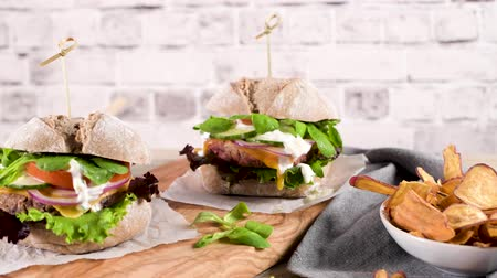 celý : Healthy vegan burger with fresh vegetables and yogurt sauce on rustic kitchen counter top.