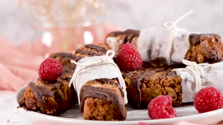tereyağı : Cereal bars with peanuts and chocolate with raspberries on kitchen counter top. Stok Video