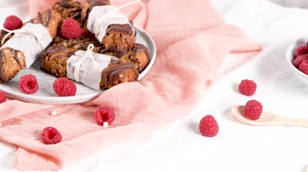 изюм : Cereal bars with peanuts and chocolate with raspberries on kitchen counter top. Стоковые видеозаписи